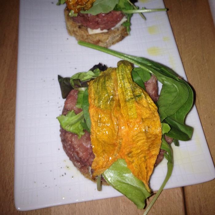 base di pane nero con Battuta di manzo all' italiana con bocconcini di mozzarella di bufala affumicata, fiori di zucca e insalatina di campo